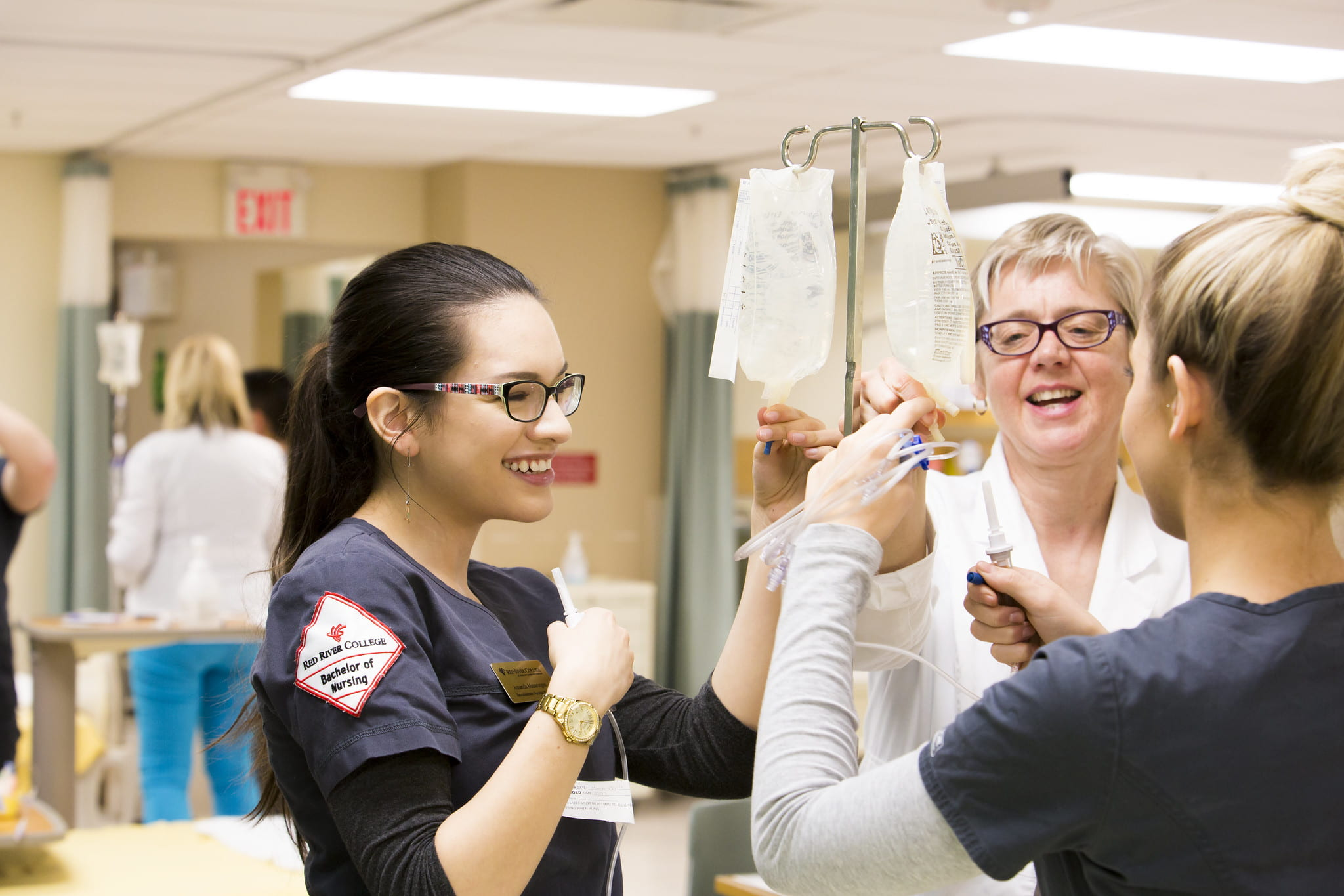 Two nursing students work with an IV supported by an instructor