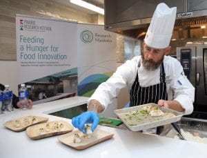 Culinary instructor plating food, Prairie Research Kitchen