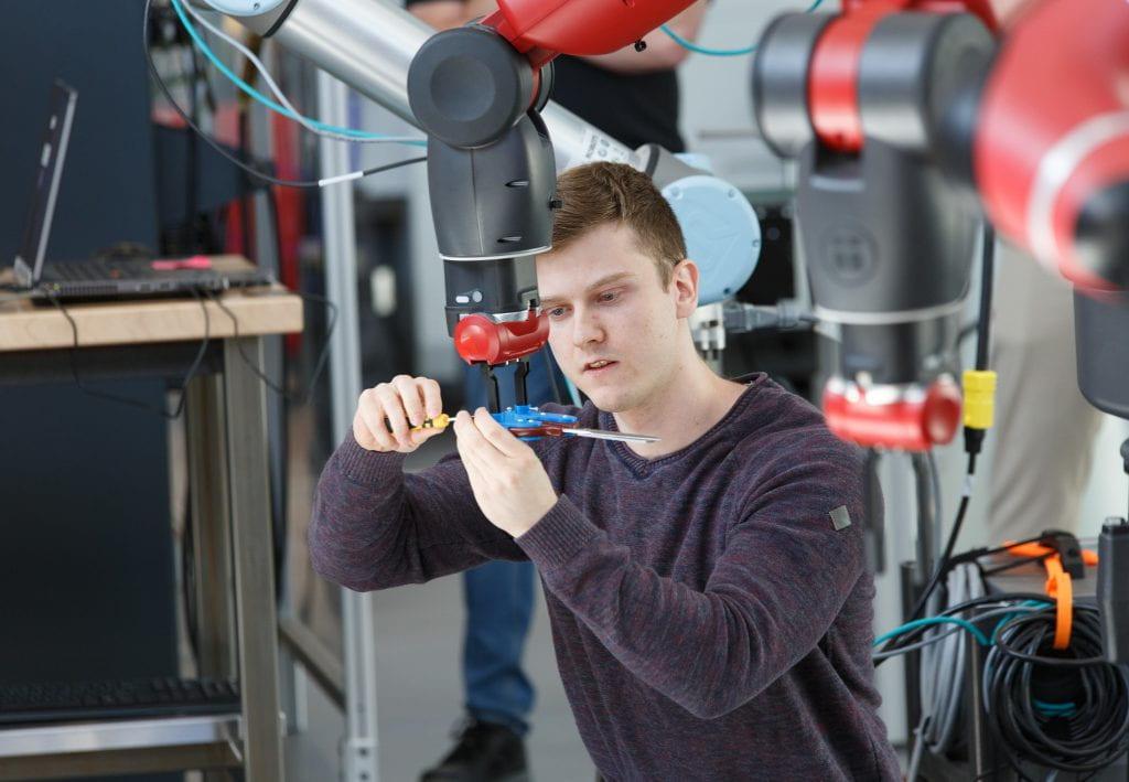 Male student adjusts collaborative robot