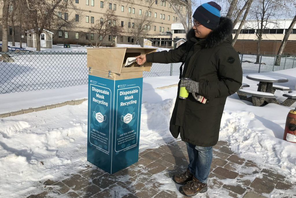 Person dropping disposable mask into recycling bin