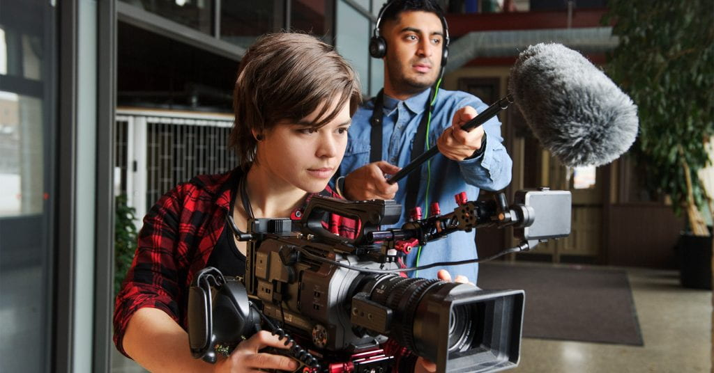 Student behind video camera, with student holding microphone