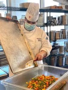 RRC Culinary Skills student Zoey Gladu prepping vegatables