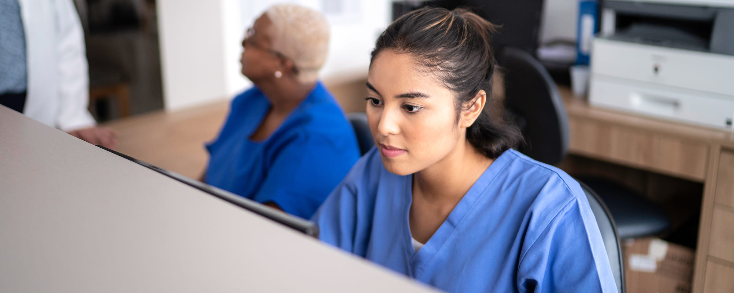 Healthcare program worker at a computer