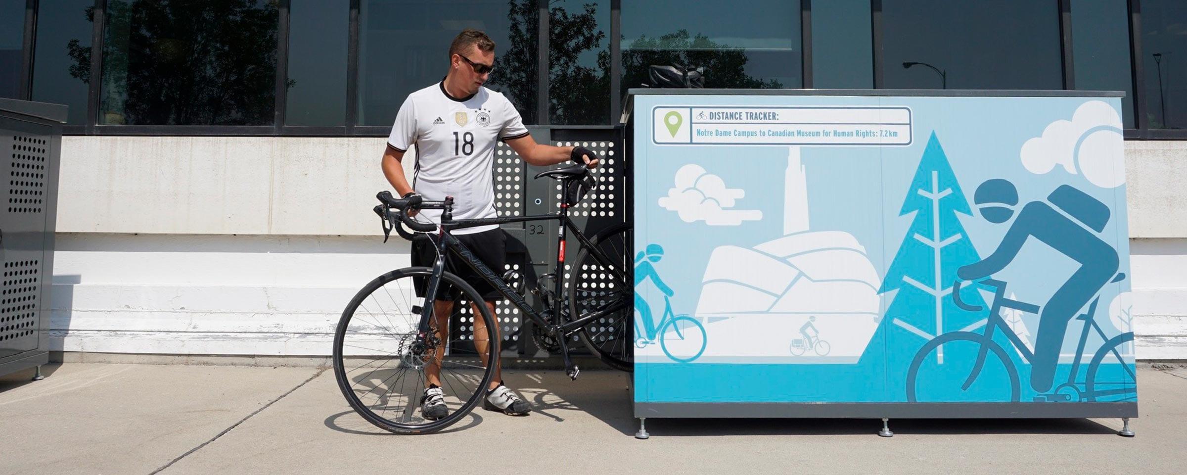 A cyclist putting their bike into a bike locker at NDC