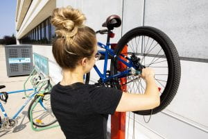 Photo of a bike up on a stand and someone tightening a screw with a wrench.