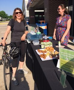 Two people, one with a bike, laughing at a table outside with pastries and juice and water.