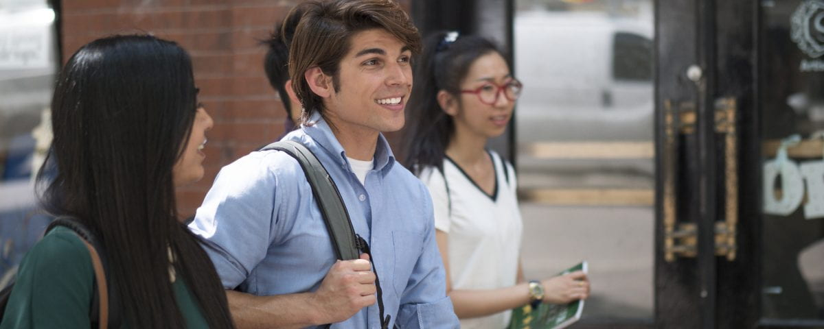 A group of students is pictured walking down a sidewalk