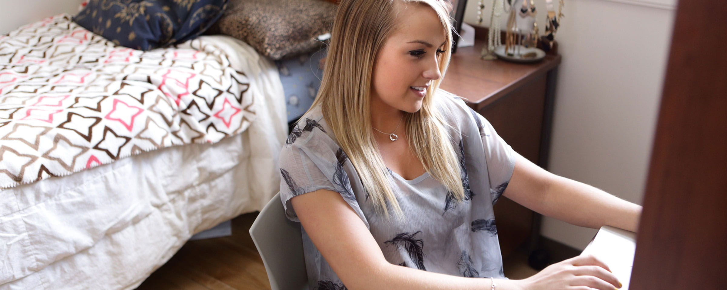 Female student working at desk in dorm room