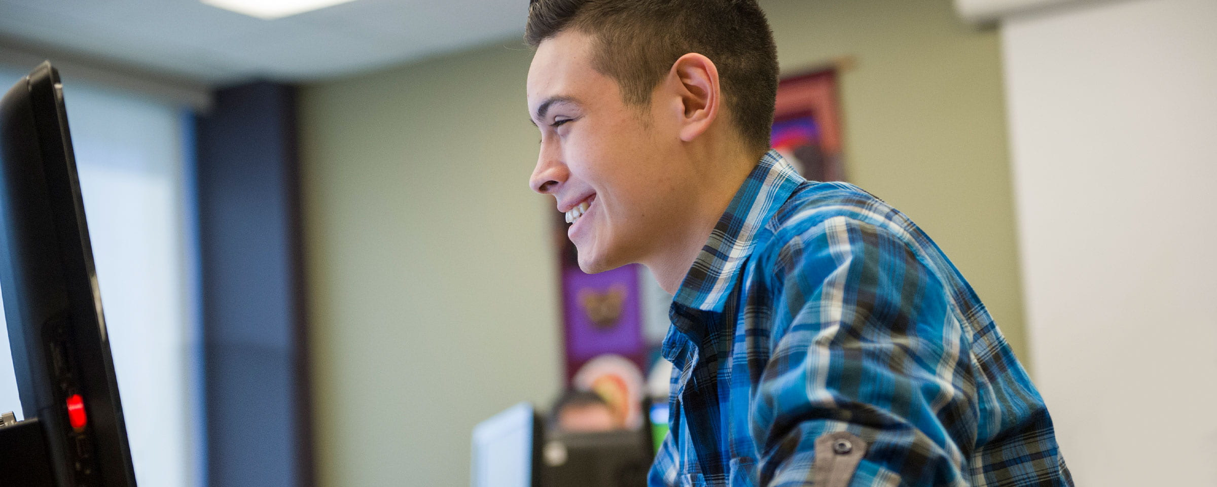 Smiling male student looking at computer screen