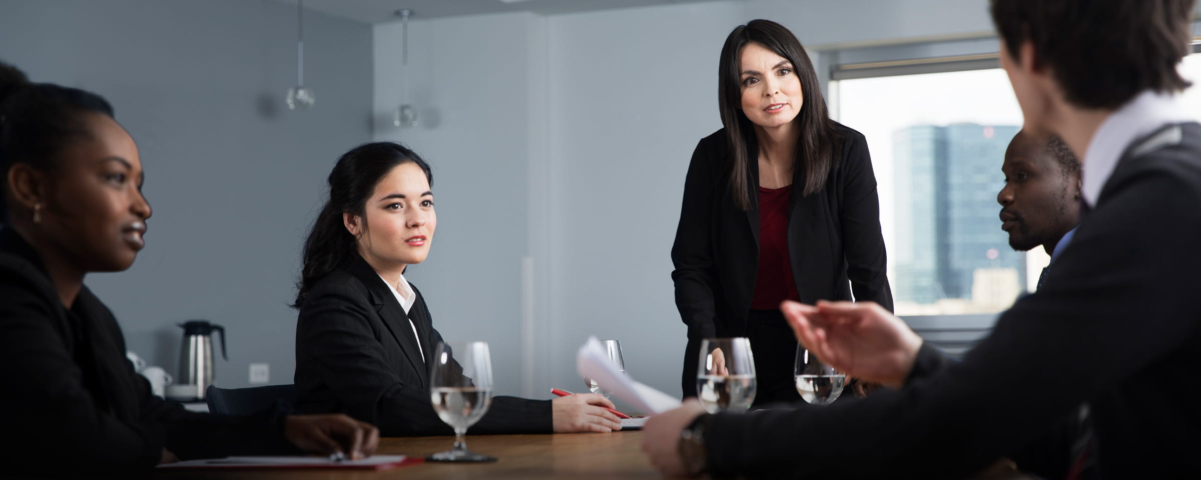 Women and men attending a boardroom business meeting