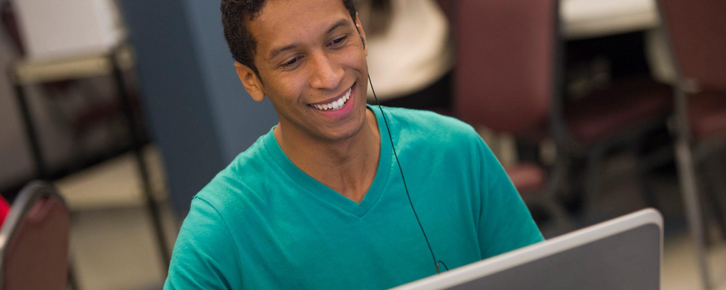 Smiling man looking at laptop screen