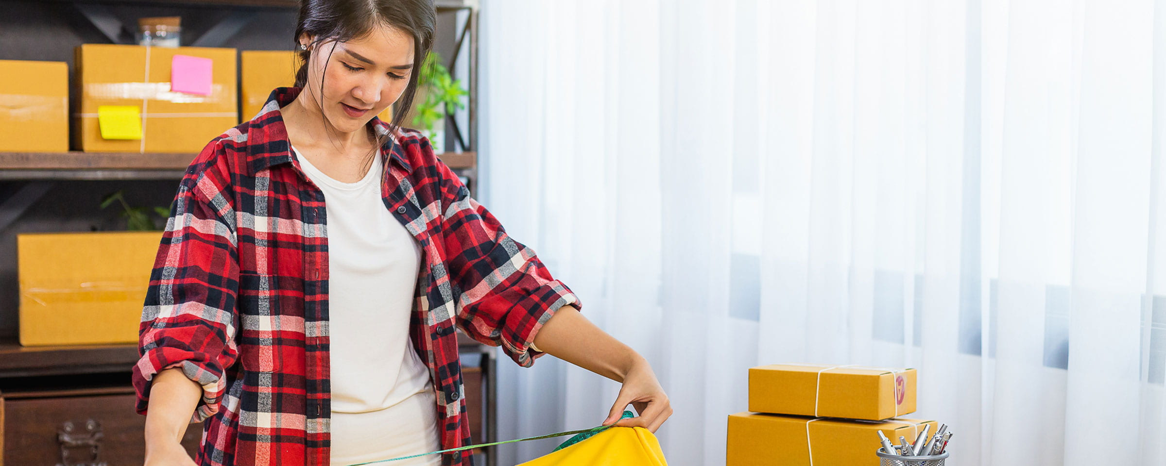 Young woman prepping packages in home office