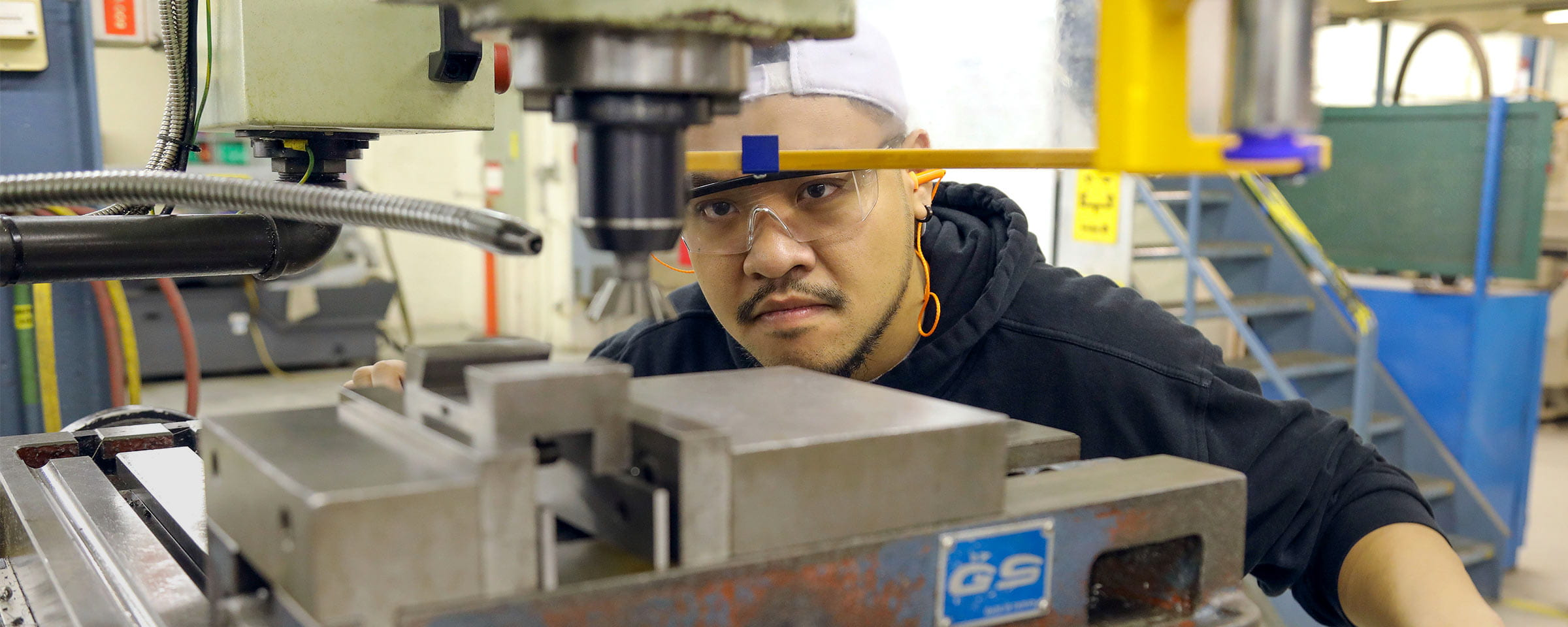 Machinist and manufacturing student at work