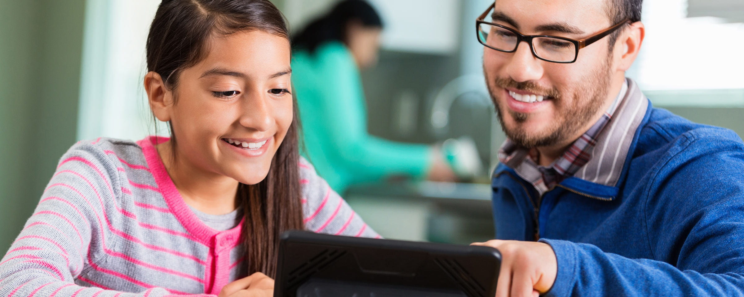 Preteen girl and father looking at tablet
