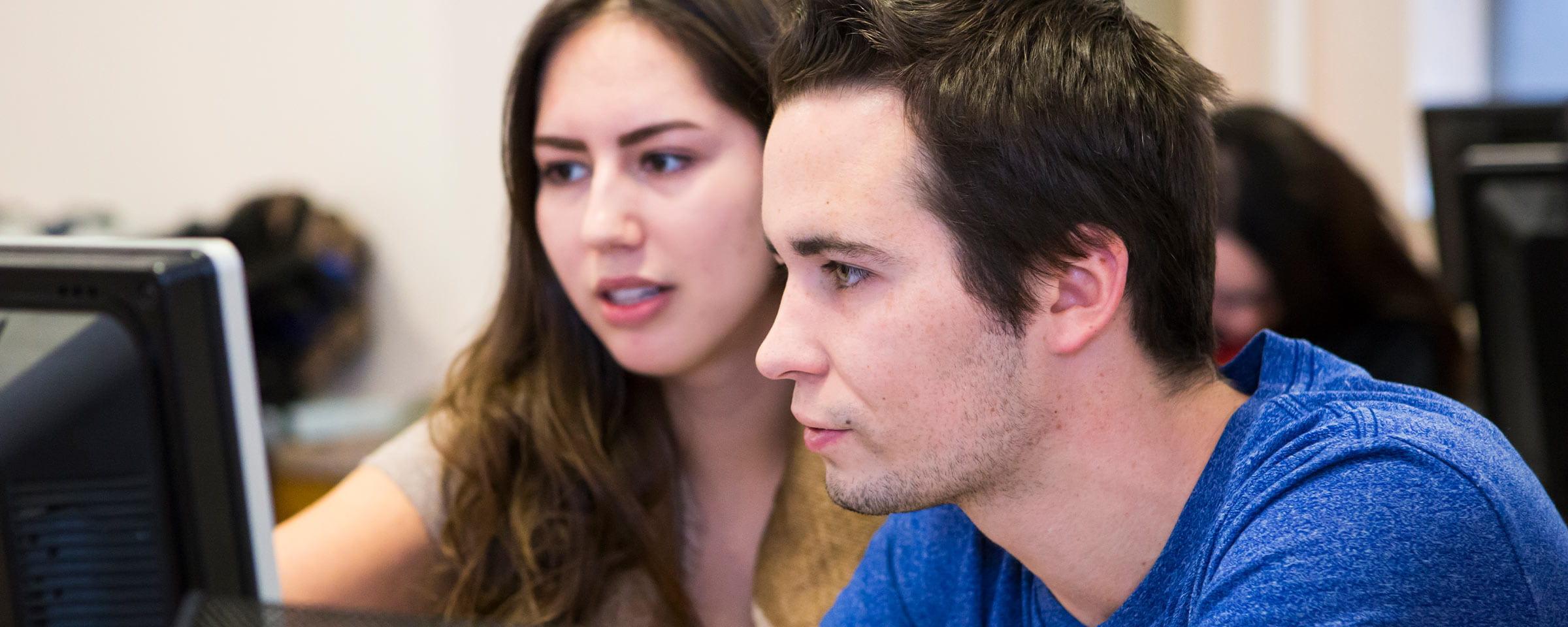 Young woman and man looking at computer screen