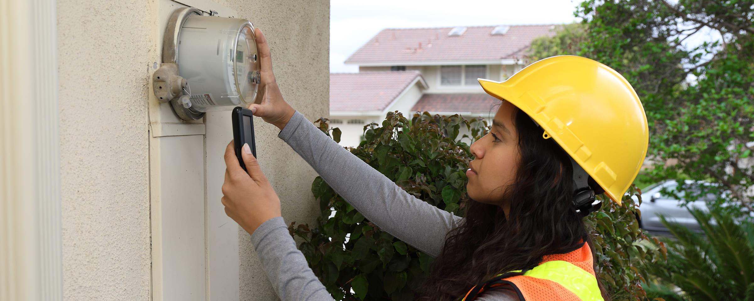 Female energy advisor taking outdoor meter reading