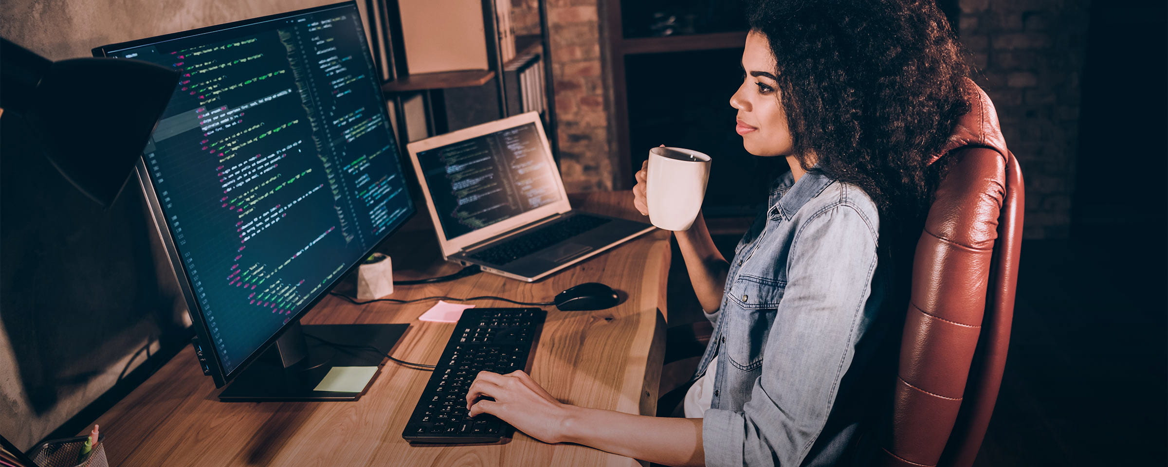 Woman drinking coffee while working on office computer