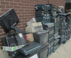 Piles of electronic waste ready to be picked up for recycling.