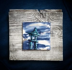 Painting in blues and white of an inuksuk mounted on wood