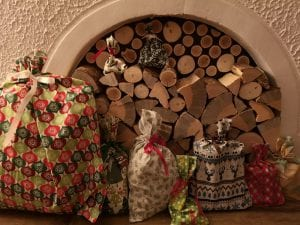 Gifts wrapped in festive fabric gift bags in front of a fireplace