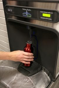 A water bottle being filled at a water bottle filling station.