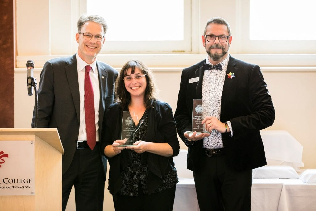Nora Sobel and Bradley West hold up their glass BRAVO awards in front of a podium with RRC President Paul Vogt.