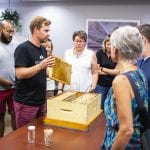 Chris Kirouac, Beeproject Apiaries, holds up a honeycomb in a demonstration at Red River College