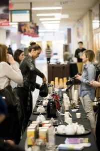 A young woman pours a sample of fair trade coffee at the fair trade coffee booth in the halls of the Notre Dame Campus.