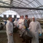 A group of students in protective gear hold up trash bags in a greenhouse.