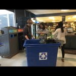 A few students do an audit of a recycling bin on campus.