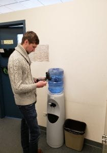A man reads a meter in front of a water cooler.