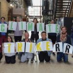 18 RRC Students and staff standing in the Roblin Atrium holding a sign that says #ClimateStrikeRRC