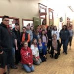 20 Staff and Students wearing green ribbons posing for a photo in the hallway outside the student lounge