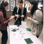 Three students cutting green circles out of felt to make pins, talking and laughing.