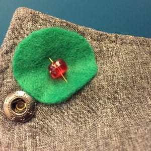 Green felt circle with a red bead pinned to a grey jacket in front of a blue background