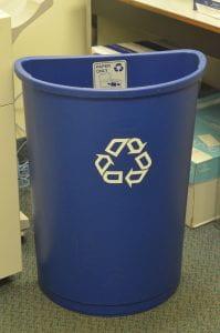 A tall, blue half moon recycling bin