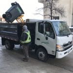 White truck lifting compost bin to dump contents