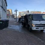 White compost truck pulls up to PGI loading dock to collect 4 compost bins