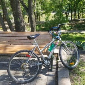 A bike learning against a bench in a park