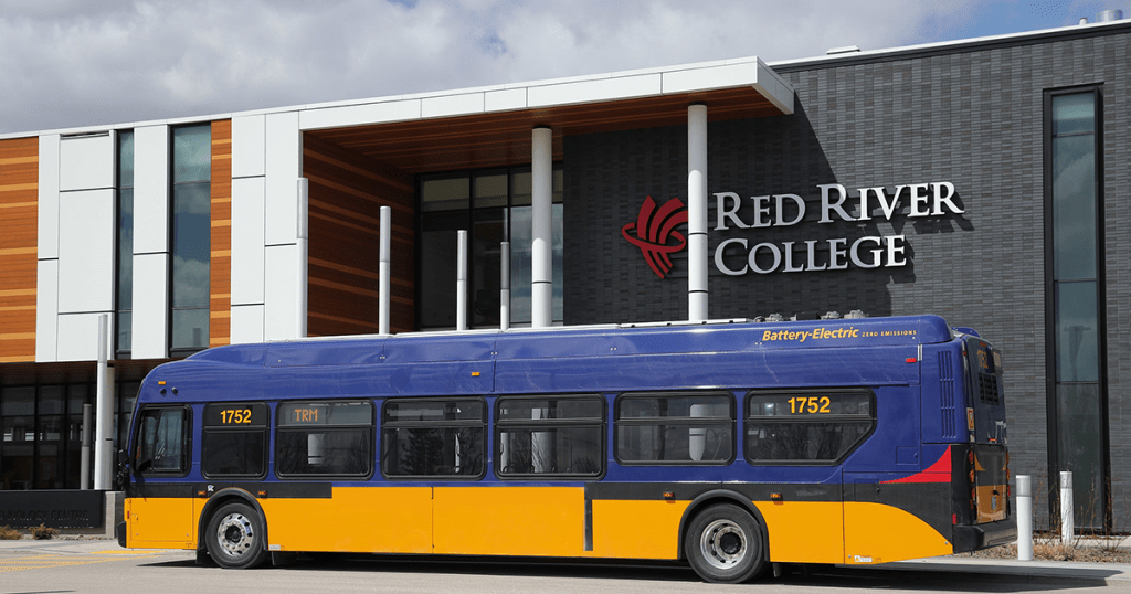 Electric bus in front of the Skilled Trades and Technology Centre building at the RRC Notre Dame Campus