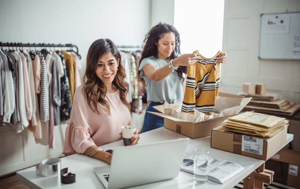 Women accepting new orders online and packing merchandise for customer