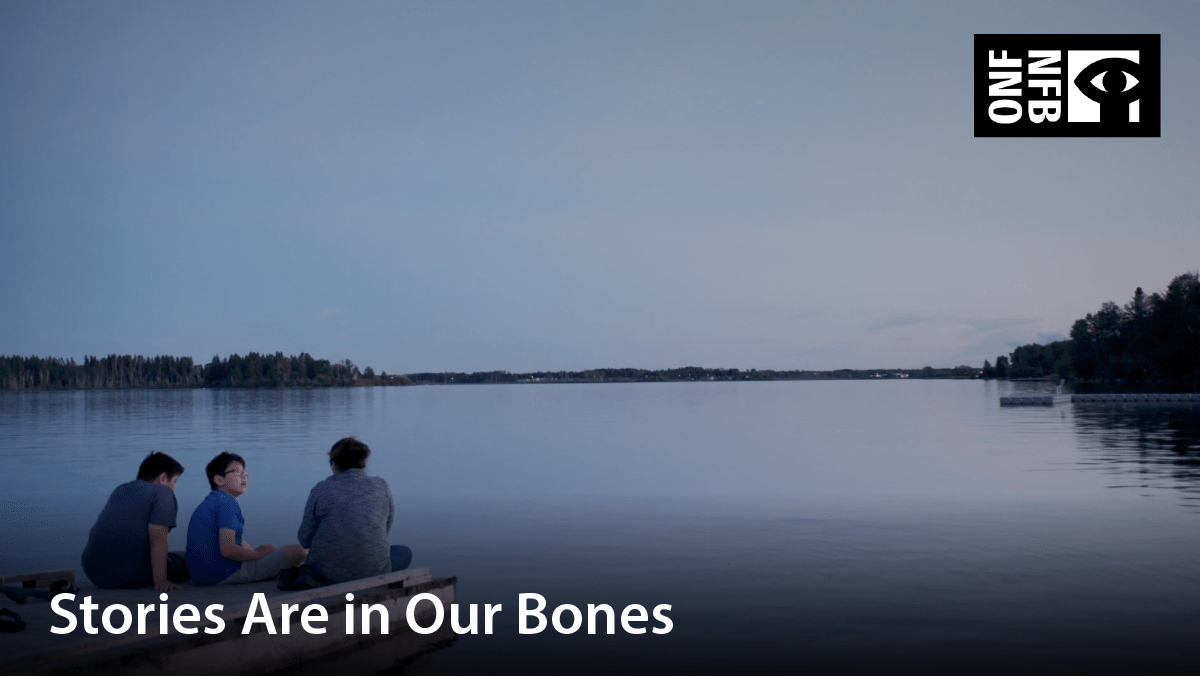 Three people sitting on the deck beside a still lake. Film title: Stories are in our bones
