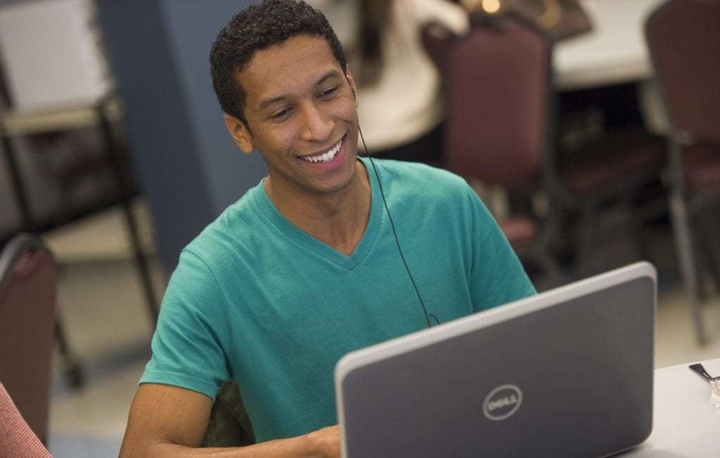 Smiling man looking at laptop screen