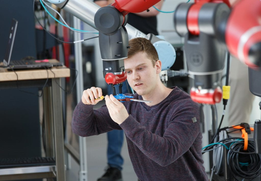 Male student adjusts collaborative robot