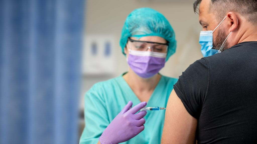 Heath-care worker administering COVID-19 vaccine
