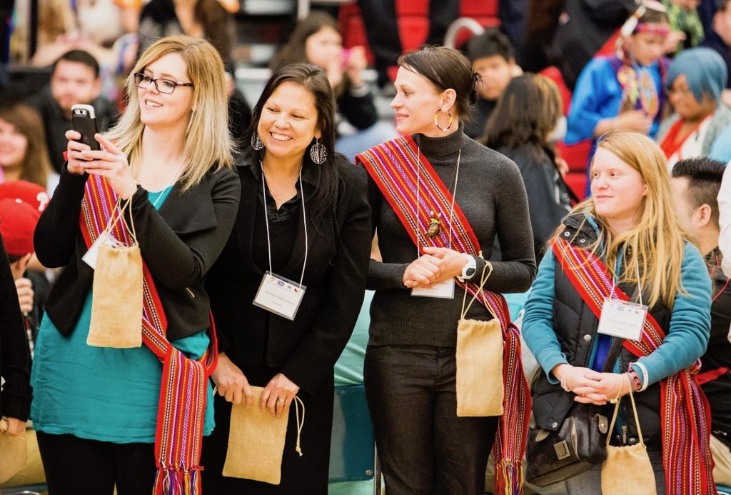 Women at graduation pow wow wearing Métis sashes