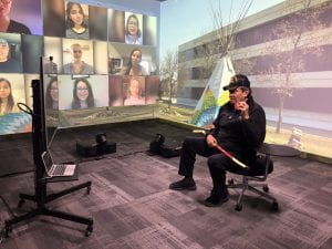 Elder Melvin Swan converses with students on digital screens