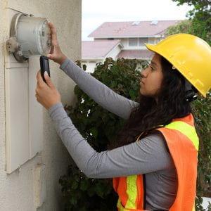 Female energy advisor takes outdoor meter reading.