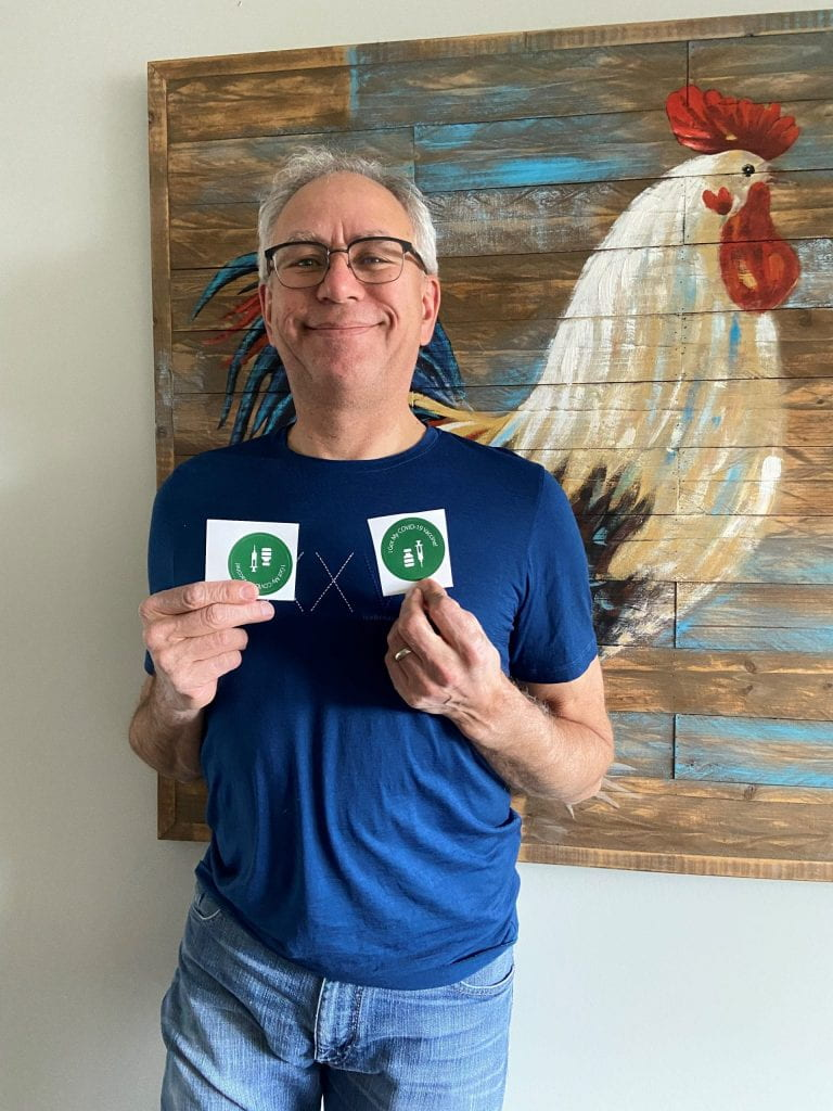 Man holding up two stickers at chest level