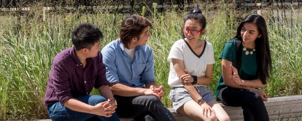 Four people sitting outside on a summer day